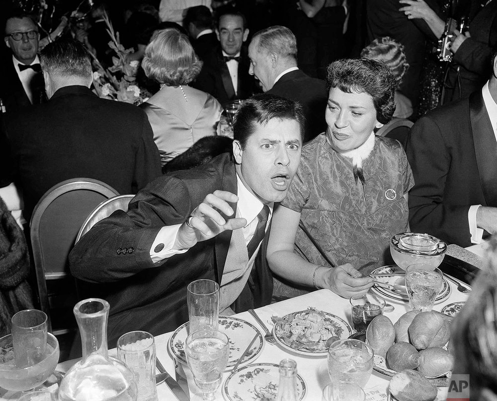 Comedian Jerry Lewis cutting up as usual.   Seated beside Jerry is his wife, Patti.    They are attending a party for Janet Leigh and Tony Curtis at Coconut Grove, Hollywood on Dec. 28, 1955 in Los Angeles.  (AP Photo/ Ed Widdis)
