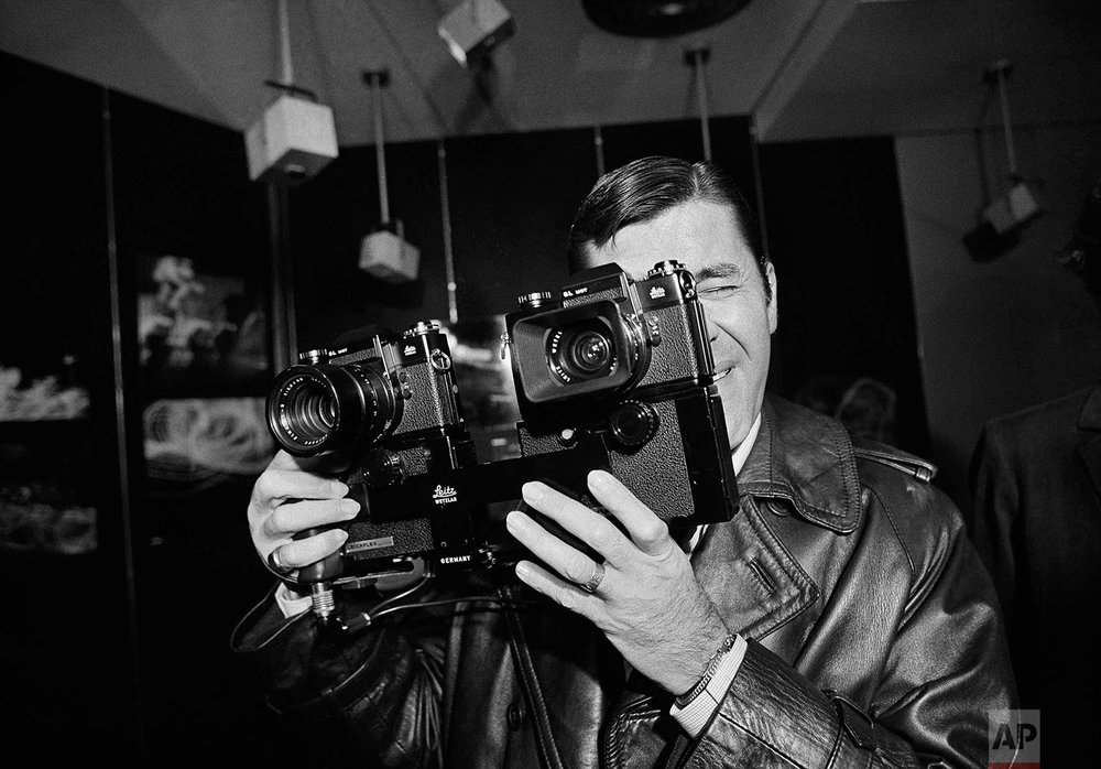 Armed with two motor-equipped cameras, American comedian Jerry Lewis, who also enjoys taking photographs takes aim it press photographers covering the first showing of his photos in a Paris gallery on March 14, 1972. (AP Photo/Laurent)