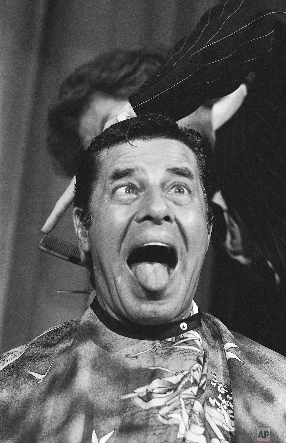 In a Oct. 16, 1977 photo, comedian Jerry Lewis cuts up during a haircut for the Muscular Dystrophy Association. Lewis was given a $250,000, the promissory note stipulating that he get his hair trimmed. (AP Photo/Phil Sandlin)