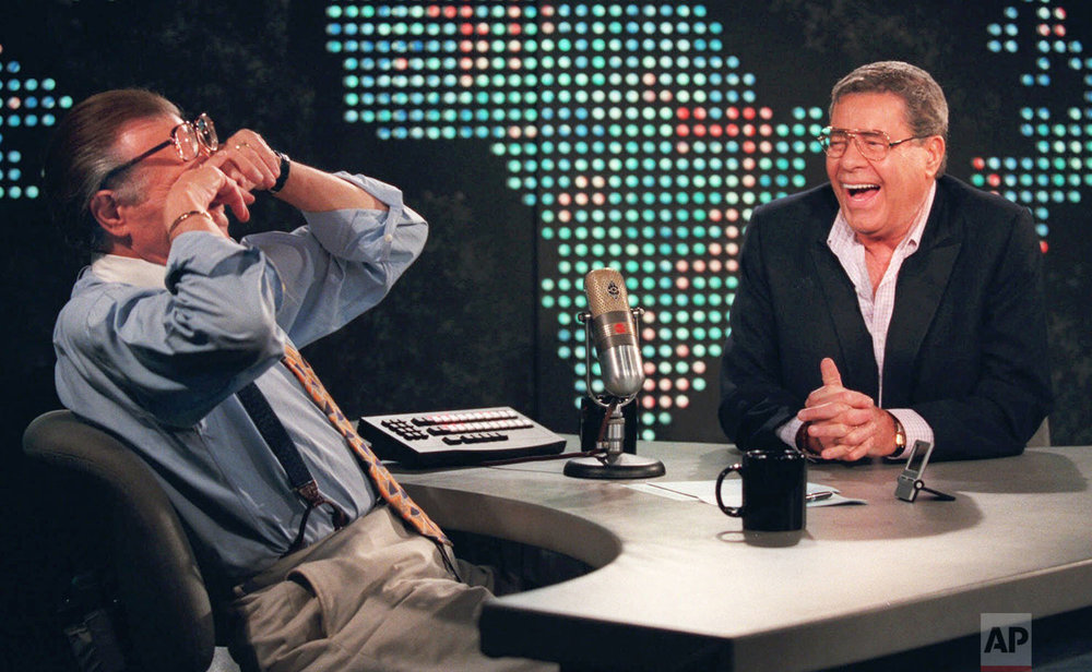 "In this Thursday, Aug. 26, 1999 photo, talk show host Larry King wipes his eyes after laughing at a joke by comedy legend Jerry Lewis, on the set of ""Larry King Live"" at CNN Studios in the Hollywood section of Los Angeles. (AP Photo/Chris Pizzello)"