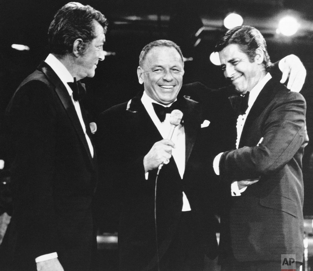 In a Sept. 6, 1976 photo, Frank Sinatra, center, appearing as a performer on the annual Muscular Dystrophy telethon hosted by Jerry Lewis, right, brings on Dean Martin, Lewis old partner, to the surprise of Lewis, in Las Vegas. It was the first time Martin and Lewis had appeared together since their comedy team broke up 20 years before. (AP Photo)