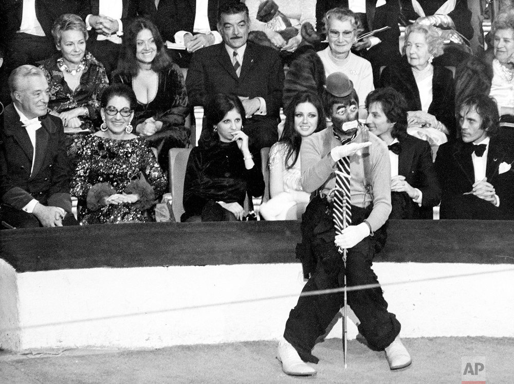 American comedian Jerry Lewis performs as a clown at the 38th Gala de L'Union des Artistes at the Cirque d'Hiver in Paris, France, April 24, 1971.  Watching in the background are, from left, Italian film director and producer Vittorio de Sicca, opera singer Maria Callas, unidentified woman, Italian actress Gigliola Cinmetti and French singer Hughes Aufray.  (AP Photo/Michel Lipchitz)