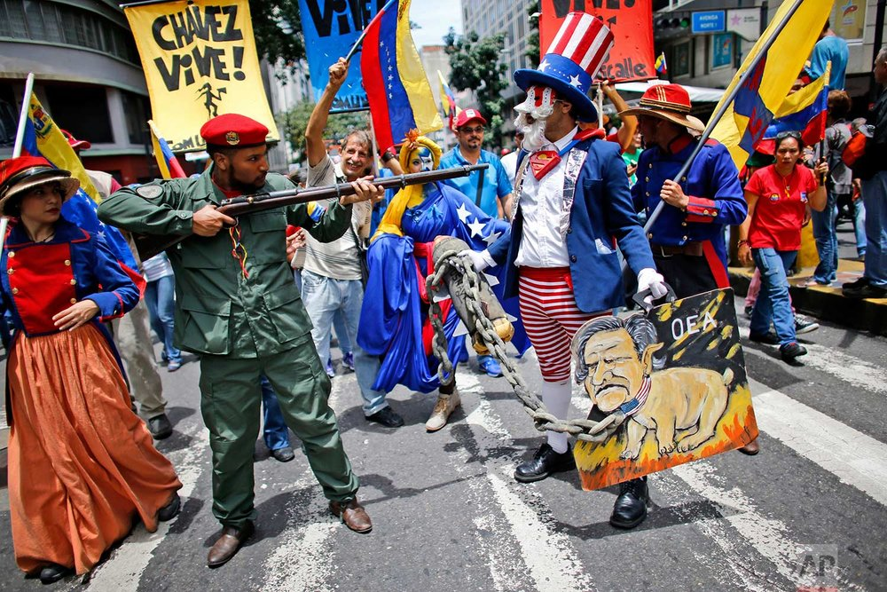 """Government supporters perform a parody involving a Venezuelan militia member confronting Uncle Sam, symbolizing the U.S. government, during an anti-imperialist march to denounce U.S. President Donald Trump's talk of a """"military option"""" for resolving the country's political crisis, in Caracas, Venezuela, Monday, Aug. 14, 2017. (AP Photo/Ariana Cubillos)"""