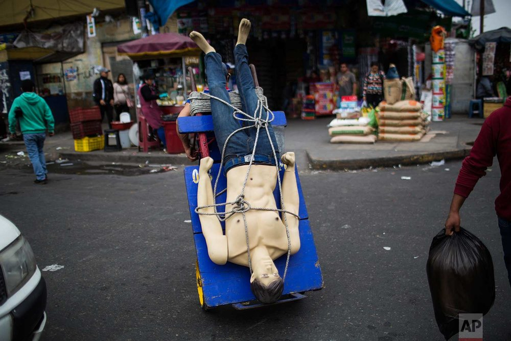 """A loader or """"cargador"""" carries a mannequin on his dolly at the Gamarra market, one of Latin America's largest and busiest textile markets, in Lima, Peru, Monday, Aug. 14, 2017. (AP Photo/Rodrigo Abd)"""