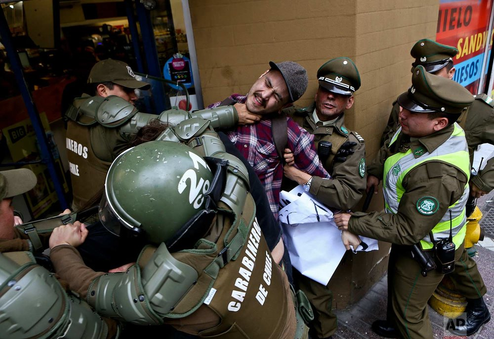 A man is detained by national police officers outside the Argentinaian consulate during a protest demanding information on the whereabouts of missing activist Santiago Maldonado, in Santiago, Chile, Thursday, Aug. 17, 2017. (AP Photo/Esteban Felix)
