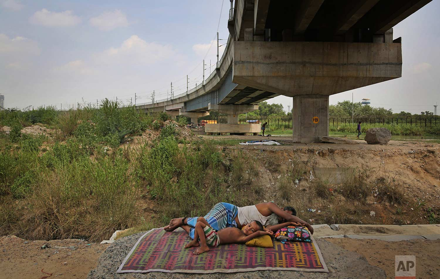 A Rohingya refugee takes a nap as a child lies next to him outside a temporary shelter in New Delhi, India, Wednesday, Aug. 16, 2017. (AP Photo/Altaf Qadri)