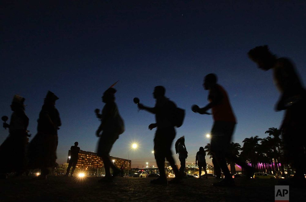Indigenous people perform a ritual dance outside the Supreme Court in Brasilia, Brazil, Tuesday, Aug. 15, 2017. (AP Photo/Eraldo Peres)
