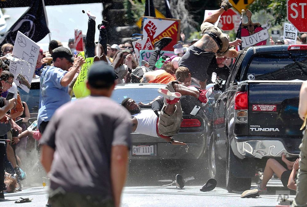 People fly into the air as a vehicle drives into a group of protesters demonstrating against a white nationalist rally in Charlottesville, Va., Saturday, Aug. 12, 2017. (Ryan M. Kelly/The Daily Progress via AP)
