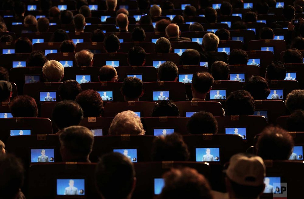South Korean President Moon Jae-in is seen on small screens as participants listen to his speech during a ceremony to celebrate Korean Liberation Day at the Seong Cultural Center in Seoul, South Korea, Tuesday, Aug. 15, 2017. (AP Photo/Ahn Young-joon)