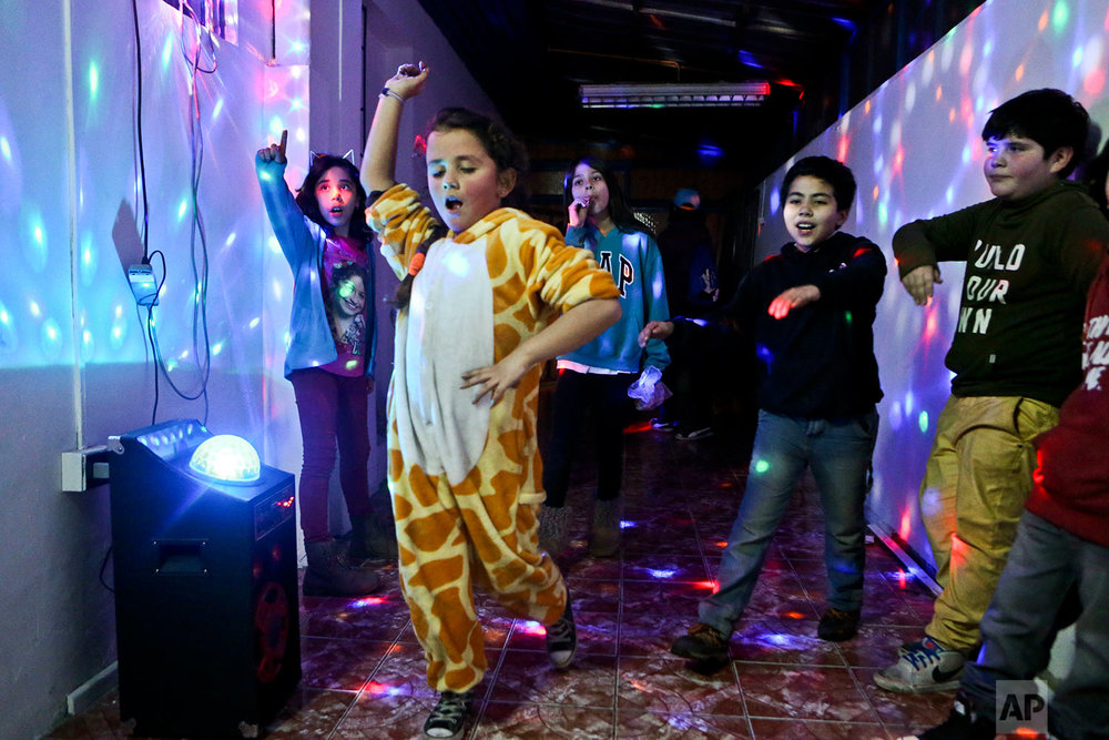 """In this July 22, 2017 photo, Selenna, sporting a giraffe costume for the fun of it, dances with other kids at the end of a gender identity workshop at a community center in Santiago, Chile. Selenna said she never liked celebrating her birthday because she would always get toy cars. """"Maybe they didn't notice it,"""" said Selenna. """"But I was always (a girl)."""" (AP Photo/Esteban Felix)"""