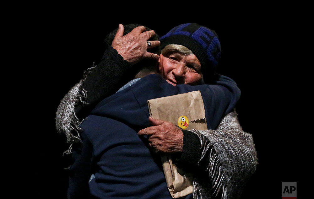 In this Aug. 19, 2017 photo, transgender boy Matias, 15, is embraced by his grandmother as they attend an event celebrating Transgender Children Day in Santiago, Chile. The families of trans children are demanding greater acceptance which has fed the broader debate about gender rights in a country so socially conservative that it legalized divorce just 13 years ago. (AP Photo/Esteban Felix)