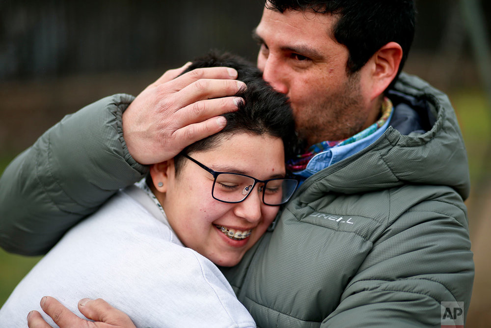In this Aug. 15, 2017 photo, transgender boy Valentin, 16, is embraced by his father Juan Carlos at a park in Santiago, Chile. Valentin and his father were at the park for a workshop that focused on gender and empowerment. (AP Photo/Esteban Felix)