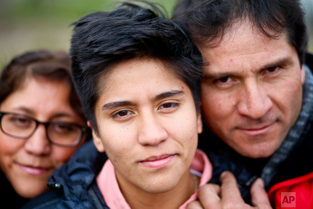 In this Aug. 15, 2017 photo, transgender boy Tobias, 16, poses for a portrait with his parents Paulina and Carlos at a park in Santiago, Chile. The family was at the park for a workshop that focused on gender and empowerment. (AP Photo/Esteban Felix)