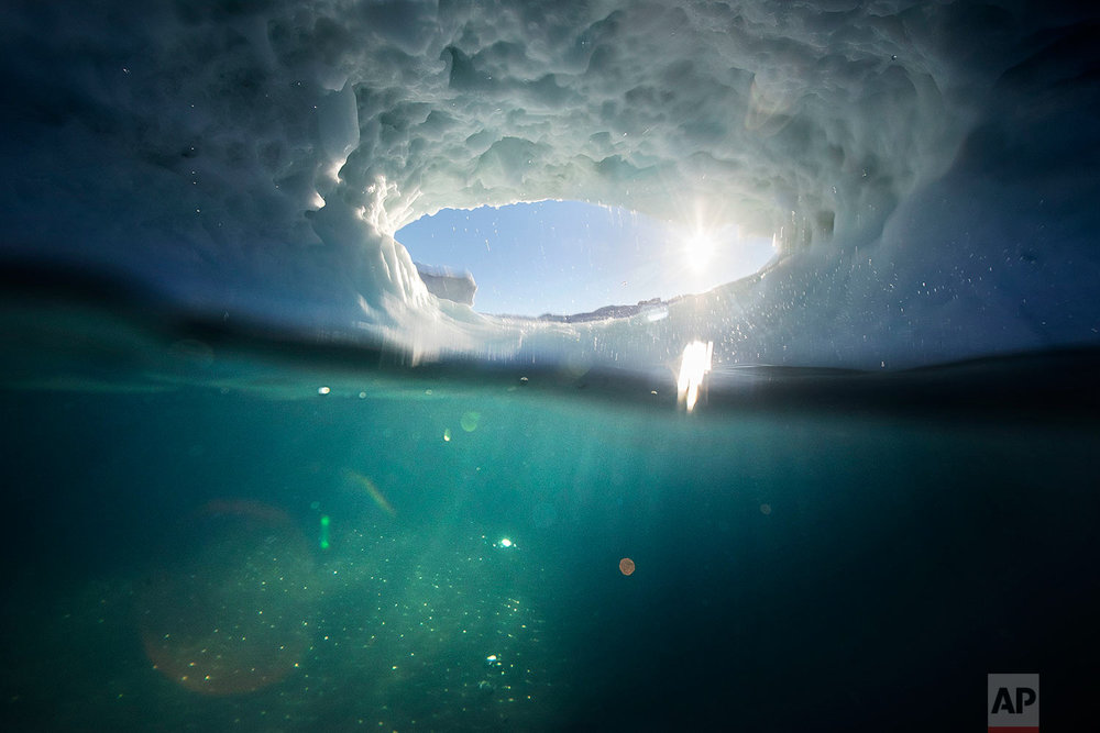 The submerged section of an iceberg is illuminated underwater by the setting sun through a hole melted in the iceberg floating in the Nuup Kangerlua Fjord near Nuuk in southwestern Greenland, Tuesday, Aug. 1, 2017. (AP Photo/David Goldman)