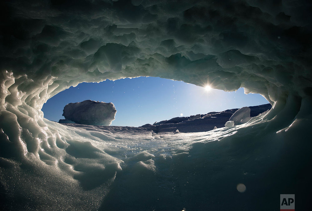 The sun sets through a hole melted in an iceberg floating in the Nuup Kangerlua Fjord near Nuuk in southwestern Greenland, Tuesday, Aug. 1, 2017. (AP Photo/David Goldman)