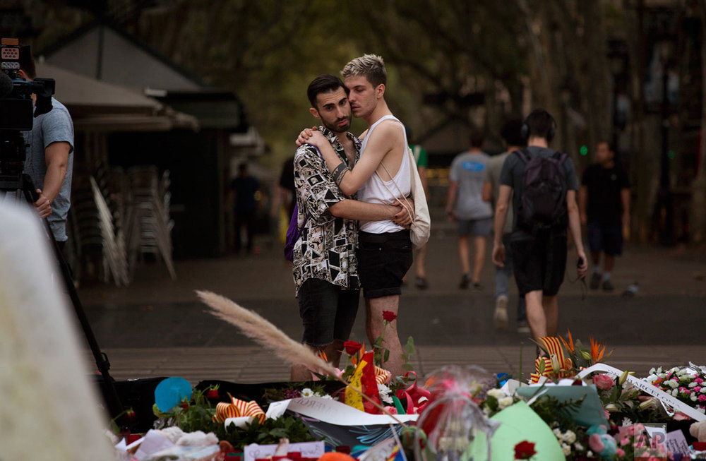 In this Monday, Aug. 21, 2017 photo, two men look at flags, messages and candles placed on the ground after a van attack that killed at least 14 people in Las Ramblas promenade in Barcelona, Spain. (AP Photo/Emilio Morenatti)