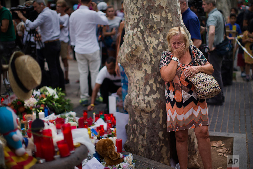 In this Saturday, Aug. 19, 2017 photo, a woman cries at a memorial tribute of flowers, messages and candles to the victims on Barcelona's historic Las Ramblas promenade, where a van attack killed at least 13 people, Spain. (AP Photo/Emilio Morenatti)