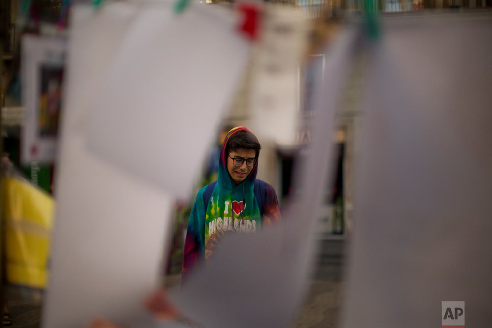 In this Monday, Aug. 21, 2017 photo, a boy cries as he reads the messages placed on the ground, after a van attack  in central Barcelona, Spain. (AP Photo/Emilio Morenatti)
