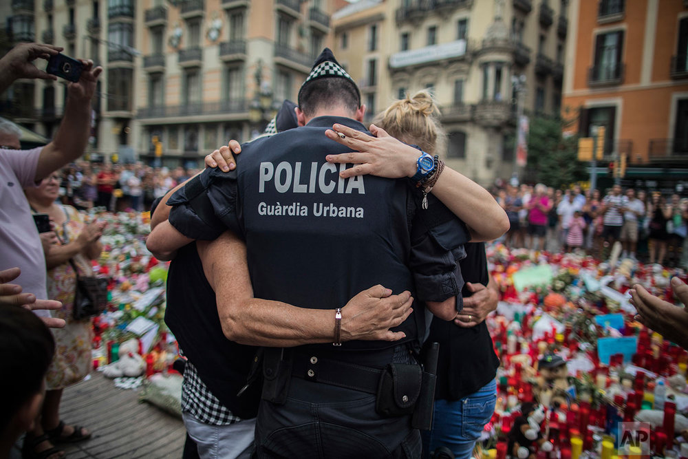 In this Monday, Aug. 21, 2017 photo, a policeman hugs a boy and his family that he helped during the terrorist attack, at a memorial to the victims on Las Ramblas, Barcelona, Spain. (AP Photo/Santi Palacios)