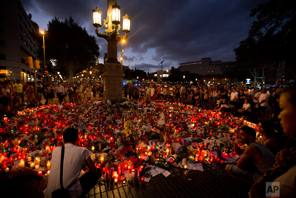 In this Sunday, Aug. 20, 2017 photo, people stand next to candles and flowers placed on the ground, after a terror attack that killed at least 14 people and wounded over 120 in Barcelona, Spain. (AP Photo/Emilio Morenatti)