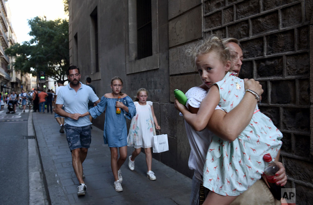 In this Thursday, Aug. 17, 2017 photo, people flee the scene in Barcelona, Spain, after a white van jumped the sidewalk in the historic Las Ramblas district, crashing into a summer crowd of residents and tourists. (AP Photo/Giannis Papanikos)