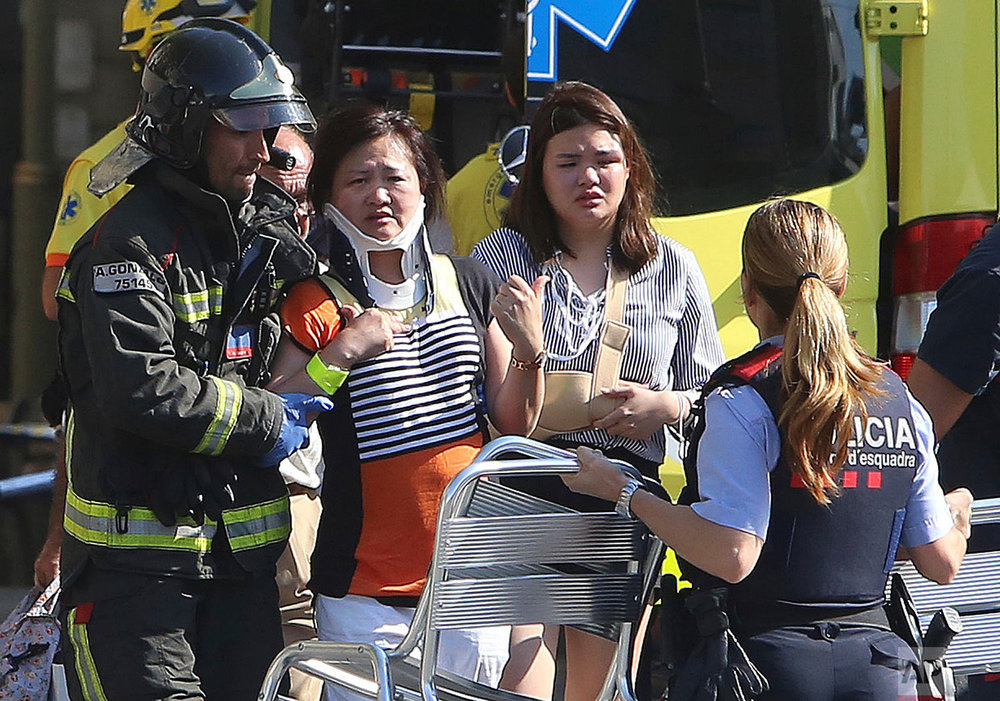 In this Thursday, Aug. 17, 2017 photo, injured people are treated after a white van jumped the sidewalk in the historic Las Ramblas district, crashing into a summer crowd of residents and tourists. (AP Photo/Oriol Duran)