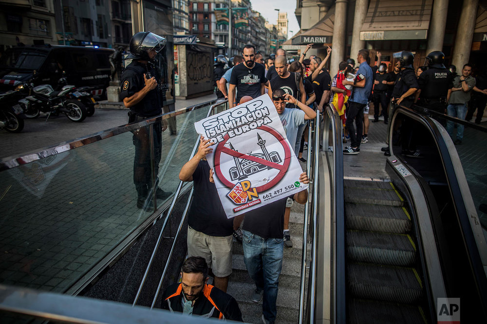 "Neo-nazis carry a banner with the slogan ""Stop islamisation of Europe"" during a fascist and Islamophobic protest in Barcelona, Spain, Friday Aug. 18, 2017. (AP Photo/Santi Palacios)"