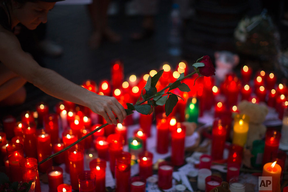 In this Friday, Aug. 18, 2017 photo, a woman places flowers on a memorial after a van attack that killed at least 13, in central Barcelona, Spain. (AP Photo/Emilio Morenatti)