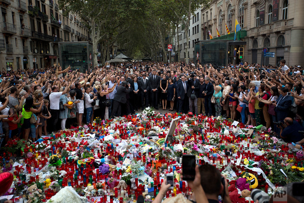 In this Saturday, Aug. 19, 2017 photo, Spain's King Felipe, centre, stands with Queen Letizia and Catalonia regional President Carles Puigdemont, centre left, at a memorial tribute of flowers, messages and candles to the van attack victims in Las Ramblas promenade, Barcelona, Spain. (AP Photo/Emilio Morenatti)