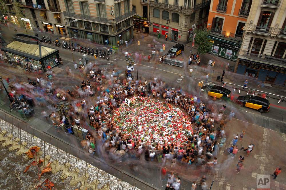 In this Saturday, Aug. 19, 2017 photo, people pay respect at a memorial tribute of flowers, messages and candles to the victims on Barcelona's historic Las Ramblas. A van veered onto a promenade and barreled down the busy walkway in central Barcelona on Thursday, swerving back and forth as it mowed down pedestrians and turned a picturesque tourist destination into a bloody killing zone.  (AP Photo/Manu Fernandez)