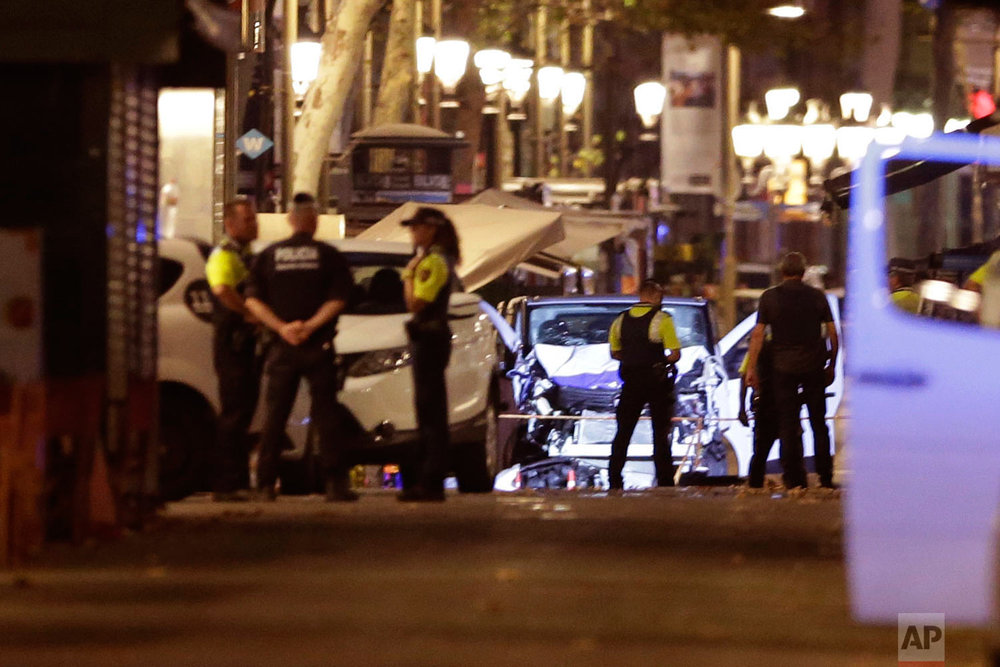 In this Thursday, Aug. 17, 2017 photo, police officers stand next to the van involved on an attack in Las Ramblas in Barcelona, Spain. (AP Photo/Manu Fernandez)