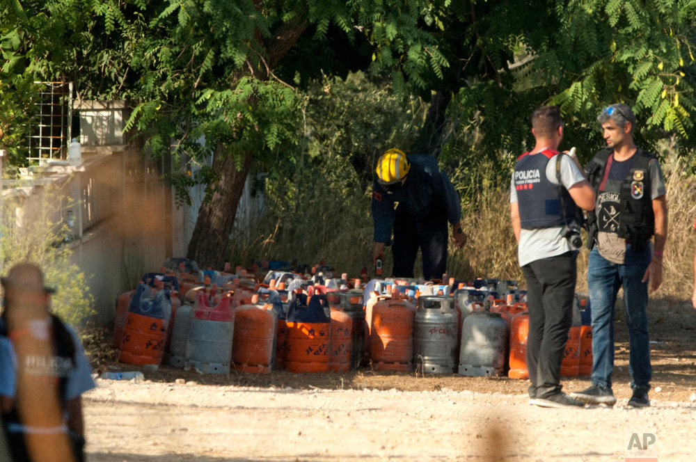 In this Friday, Aug. 18, 2017 photo, fire fighter members collect gas canisters at the explosion site where the attacks of Barcelona were planned, in Alcanar, Tarragona province. (AP Photo/Joan Revillas)