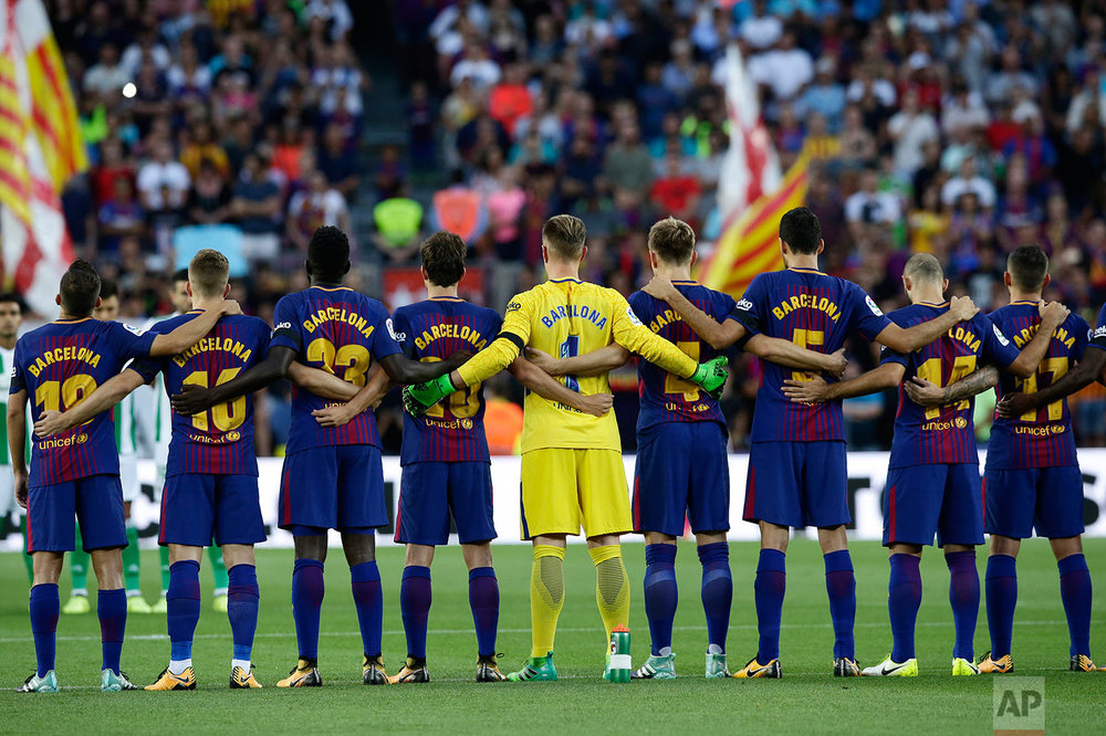 In this Sunday, Aug. 20, 2017 photo, Barcelona players stand for a minute of silence for the victims of the van attacks before a La Liga soccer match between Barcelona and Betis at the Camp Nou stadium in Barcelona, Spain. (AP Photo/Manu Fernandez)