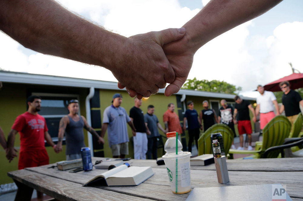 In this Thursday, July 6, 2017 photo, recovering addicts join hands during a meeting at Recovery Boot Camp, in Delray Beach, Fla. (AP Photo/Lynne Sladky)