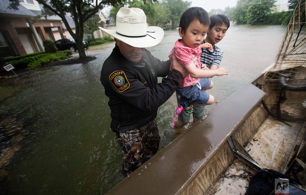 Fort Bend County Sheriff Troy Nehls and Lucas Wu lift Ethan Wu into an airboat as they are evacuated from rising waters from Tropical Storm Harvey, at the Orchard Lakes subdivision on Sunday, Aug. 27, 2017, in unincorporated Fort Bend County, Texas. (Brett Coomer/Houston Chronicle via AP)