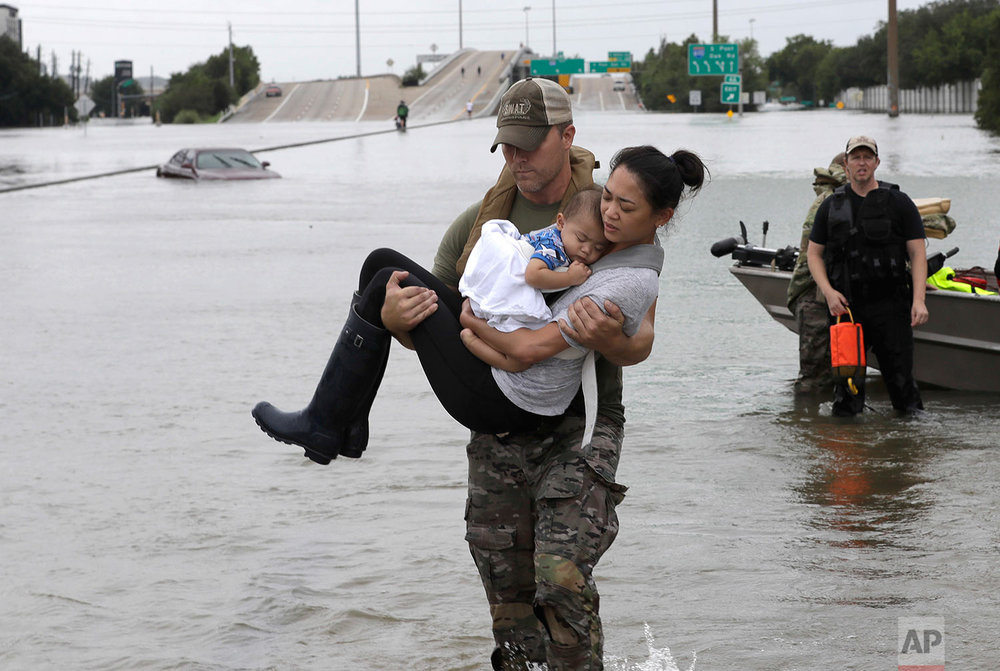 Houston Police SWAT officer Daryl Hudeck carries Connie Pham and her 13-month-old son Aiden after rescuing them from their home surrounded by floodwaters from Tropical Storm Harvey Sunday, Aug. 27, 2017, in Houston. (AP Photo/David J. Phillip)