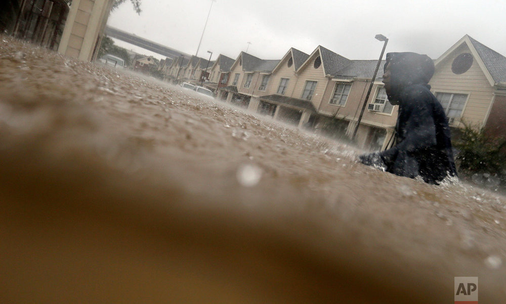 A child makes his way through floodwaters from Tropical Storm Harvey while checking on neighbors at his apartment complex in Houston, Sunday, Aug. 27, 2017. (AP Photo/LM Otero)