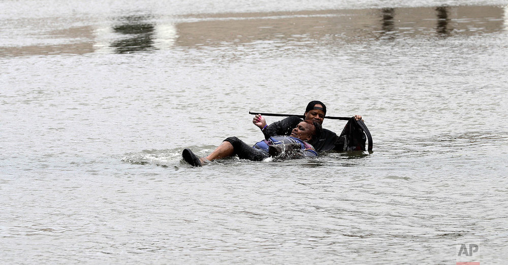 A man helps a woman in floodwaters from Tropical Storm Harvey Sunday, Aug. 27, 2017, in Houston, Texas. (AP Photo/David J. Phillip)