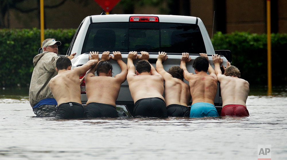People push a stalled pickup through a flooded street in Houston, after Tropical Storm Harvey dumped heavy rains Sunday, Aug. 27, 2017. (AP Photo/Charlie Riedel)