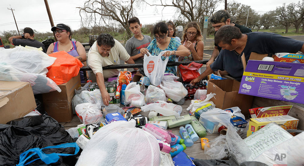 Residents pick through needed items at a make-shift aid station, Sunday, Aug. 27, 2017, in Rockport, Texas. A group from the Texas Rio Grande Valley created the station for those in need following Hurricane Harvey. (AP Photo/Eric Gay)
