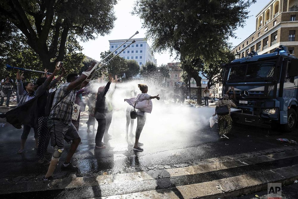Law enforcement officers use water cannons to disperse migrants in downtown Rome, Thursday, Aug. 24, 2017. Protests erupted as police continued an operation to evict some 800 Eritrean and Ethiopian refugees from a building they have occupied since 2013, despite protests from the U.N. refugee agency, UNICEF, and humanitarian organizations. (Angelo Carconi/ANSA via AP)