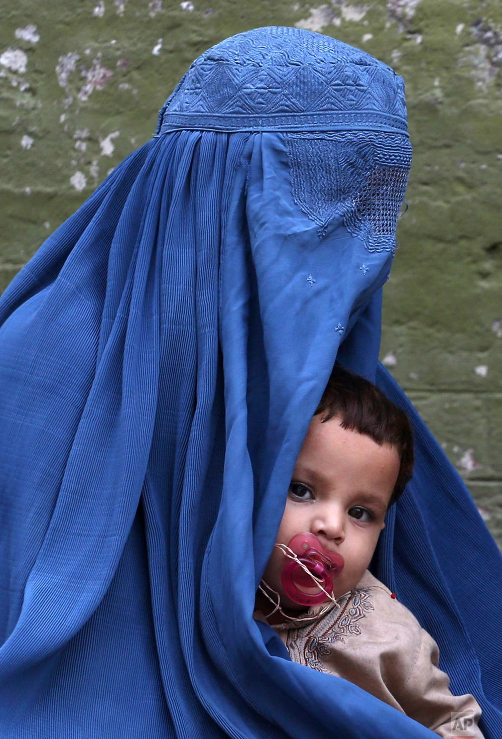 An Afghan refugee mother who fled her country due to war and famine waits with her child, to get registered in Peshawar, Pakistan, Monday. Aug. 21, 2017. (AP Photo/Muhammad Sajjad)