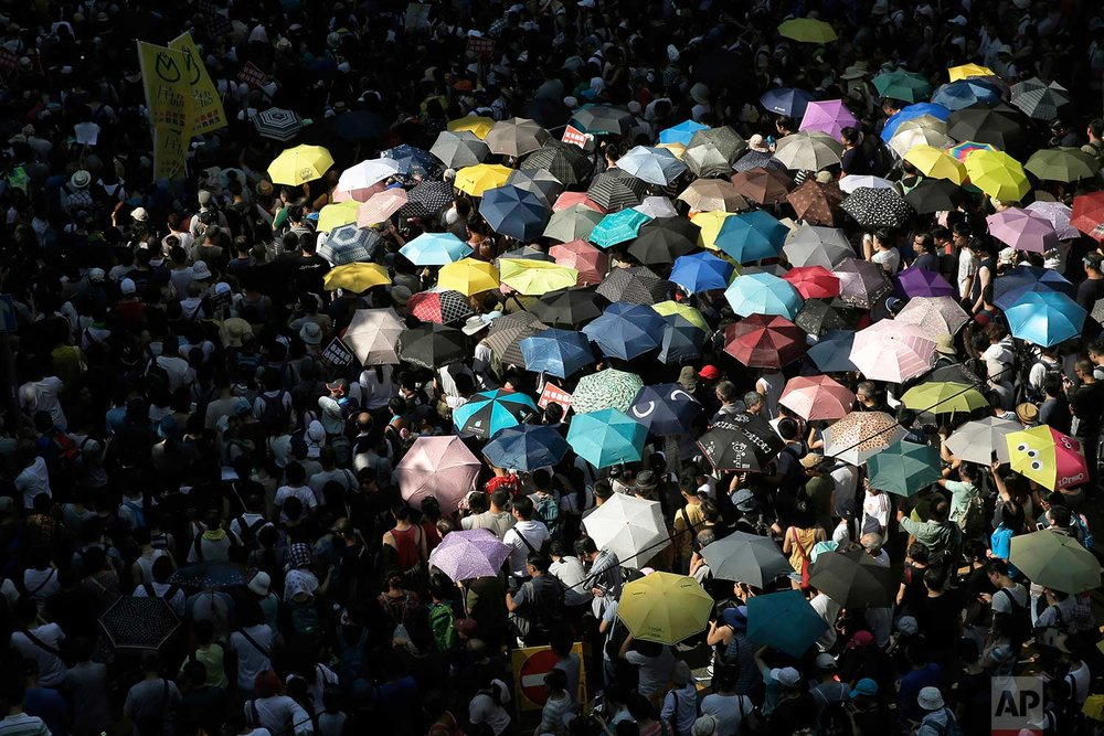 Protesters attend a rally to support young activists Joshua Wong, Nathan Law and Alex Chow in downtown Hong Kong Sunday, Aug. 20, 2017. (AP Photo/Kin Cheung)