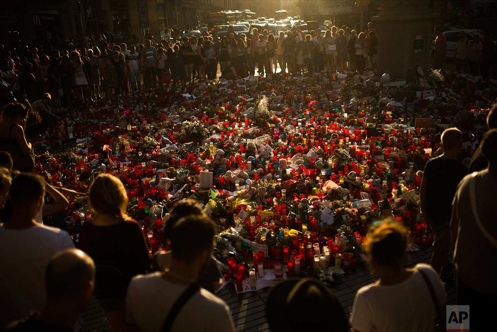 People stand next to candles and flowers placed on the ground for the victims of the fatal terrorist attack in Barcelona, Spain, Thursday, Aug. 24, 2017. (AP Photo/Francisco Seco)