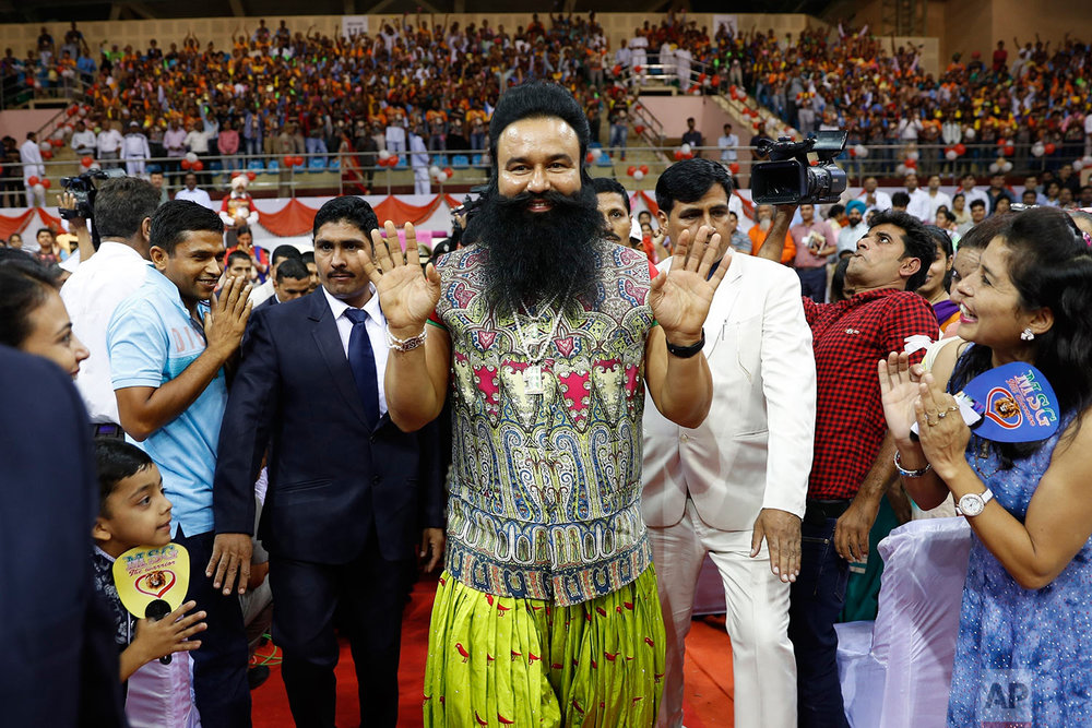 "In this Oct. 5, 2016 photo, Indian spiritual guru who calls himself Dr. Saint Gurmeet Singh Ram Rahim Insan, center, greets followers as he arrives for a press conference ahead of the release of his new movie ""MSG, The Warrior Lion Heart,"" in New Delhi, India. (AP Photo/Tsering Topgyal)"