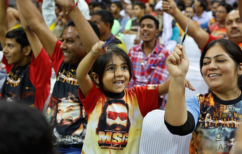 "In this Oct. 5, 2016 photo, a child wears a T-shirt with a portrait of Indian spiritual guru, who calls himself Dr. Saint Gurmeet Singh Ram Rahim Insan, during a press conference ahead of the release of the guru's film ""MSG, The Warrior Lion Heart,"" in New Delhi, India. (AP Photo/Tsering Topgyal)"