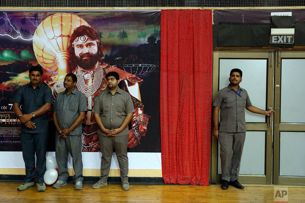 "In this Oct. 5, 2016, file photo, security officers stand watch by a poster of Indian spiritual guru, who calls himself Dr. Saint Gurmeet Singh Ram Rahim Insan, during a press conference ahead of the release of the guru's film ""MSG, The Warrior Lion Heart,"" in New Delhi, India. (AP Photo/Tsering Topgyal)"