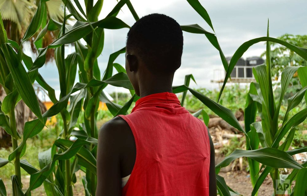 In this photo taken Sunday, July 30, 2017, Eliza, 17, who at age 13 was forced by her father to marry a 35-year-old man from their village in exchange for 50 cattle, stands next to crops in a courtyard in the town of Rumbek, South Sudan. (AP Photo/Mariah Quesada)