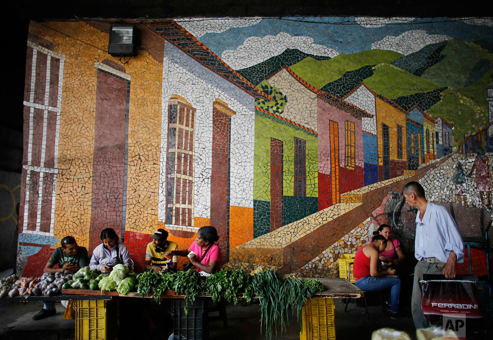 Vegetable vendors wait for customers behind their tables set up on the sidewalk, in front of a mosaic, Aug. 23, 2017, Caracas, Venezuela. (AP Photo/Ariana Cubillos)