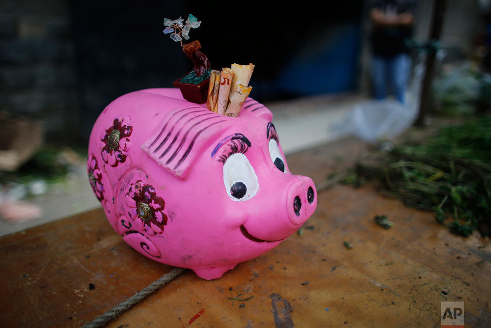 A piggy bank for tips, filled with 5 Bolivar bills, sits on the table of a vegetable vendor at a market, Aug. 23, 2017, Caracas, Venezuela. (AP Photo/Ariana Cubillos)